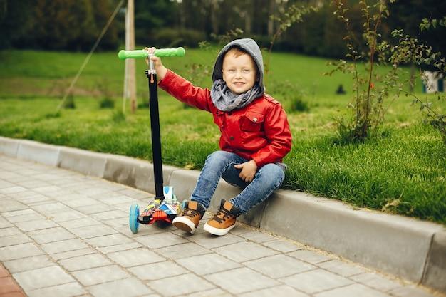 Bonita criança em um parque brincando em uma grama Foto gratuita
