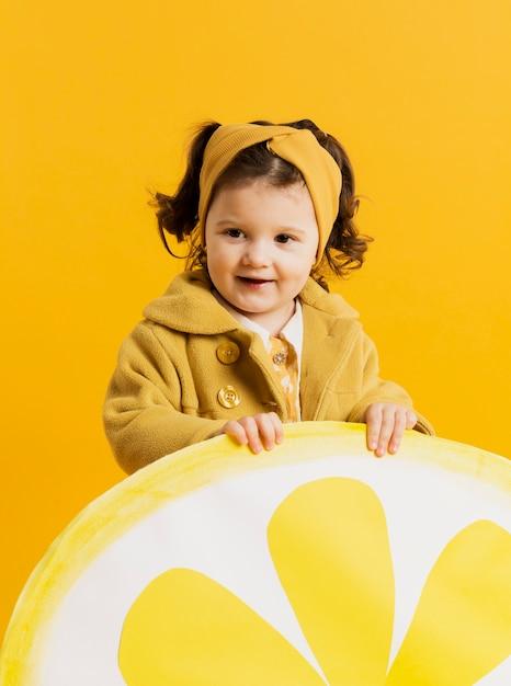 Bonita criança posando enquanto segura a fatia de limão decoração Foto gratuita