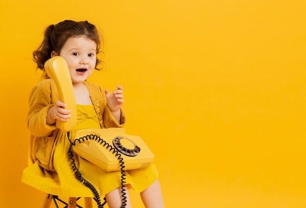Bonita criança segurando o telefone enquanto posava Foto gratuita