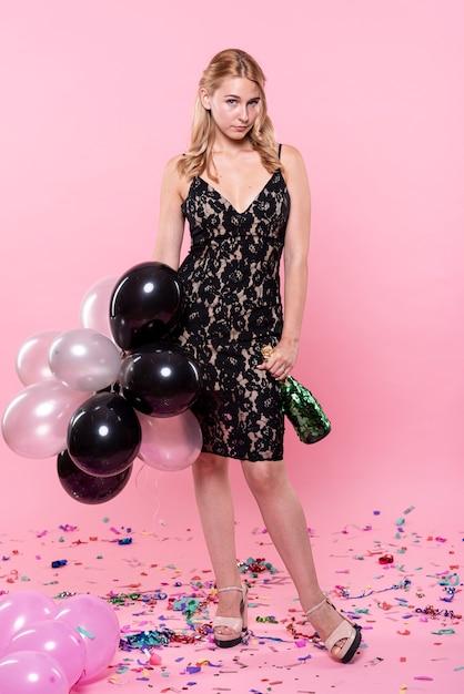 Bonita dama segurando balões e champanhe Foto gratuita