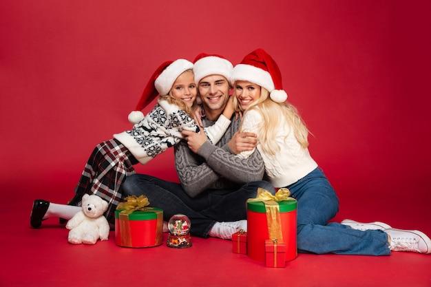 Bonita e jovem família feliz usando chapéus de natal sentado isolado Foto gratuita