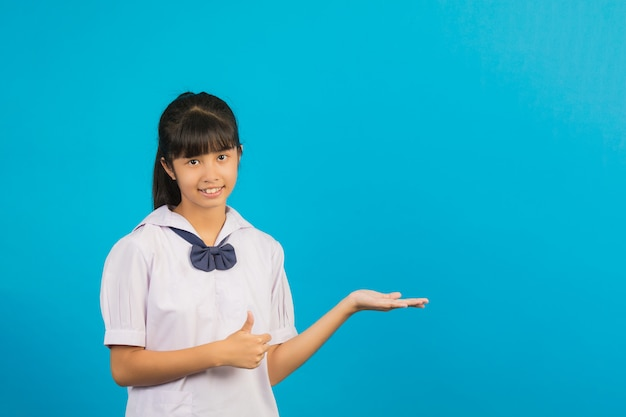 Bonita estudante asiática fazendo um polegar para cima gesto e abra sua mão no azul. Foto gratuita