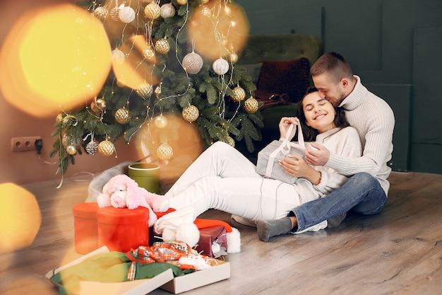 Bonita família sentada em casa perto de árvore de natal Foto gratuita
