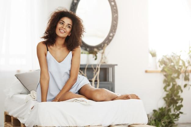 Bonita mulher africana macia em roupa de noite, sentado na cama em casa, sorrindo, sonhando, pensando em seu apartamento espaçoso. Foto gratuita