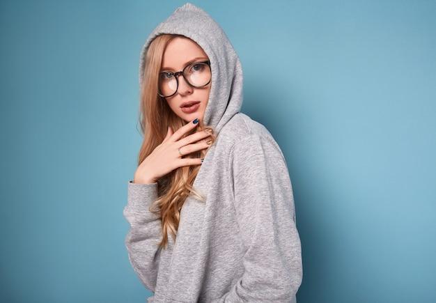 Bonita mulher loira positiva com capuz cinza e óculos Foto Premium