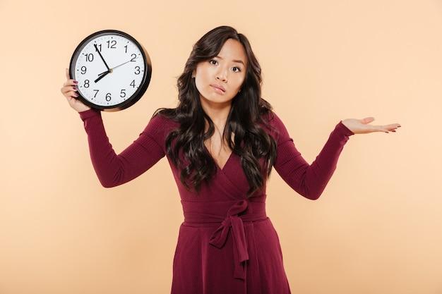 Bonita mulher morena com cabelos compridos encaracolados, segurando o relógio mostrando quase 8 atrasos ou falta algo vomitando mão sobre fundo pêssego Foto gratuita