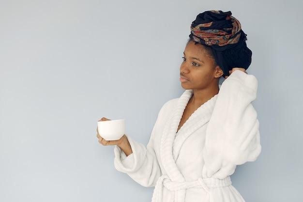 Bonita mulher negra em pé em uma parede branca Foto gratuita