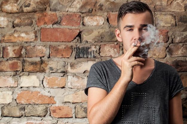 Bonitão, fumando perto da parede Foto gratuita