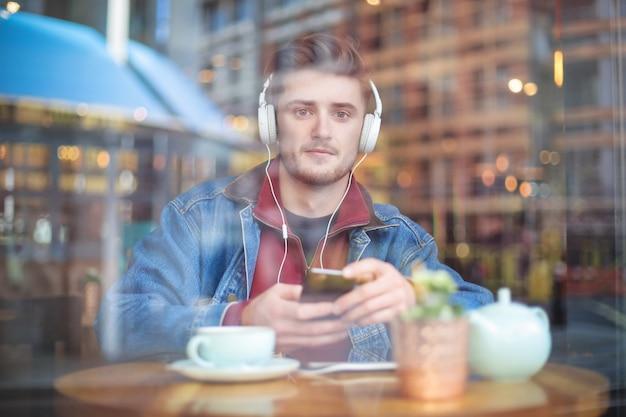 Bonitão, sentado em um bar, ouvindo algo com fones de ouvido Foto Premium