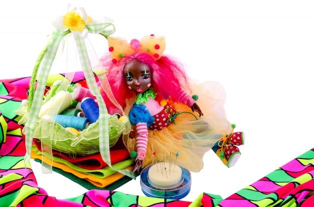 Bonitinha boneca senta-se de cima para pedaços de pano colorido, ao lado pinos, pano multicolorido. Foto Premium