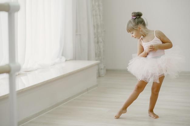 Bonitinhas bailarinas em traje de balé rosa. criança com sapatilhas de ponta está dançando na sala. criança na aula de dança. Foto gratuita