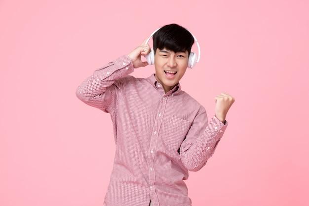 Bonitinho sorrindo homem asiático usando fones de ouvido, ouvindo música Foto Premium