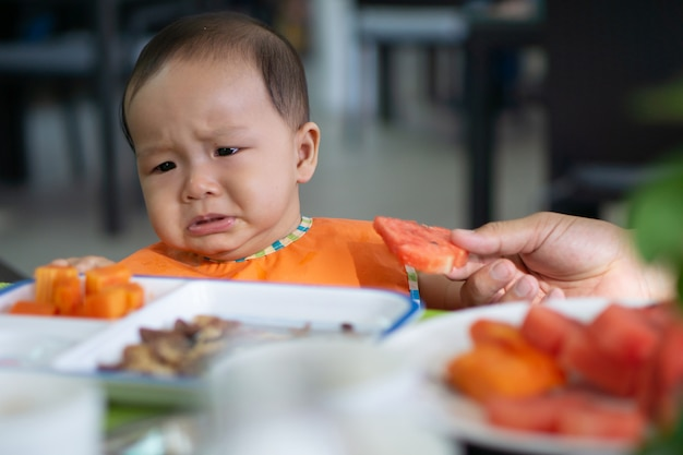 Bonito 5-6 meses menina asiática não quer comer melancia Foto Premium
