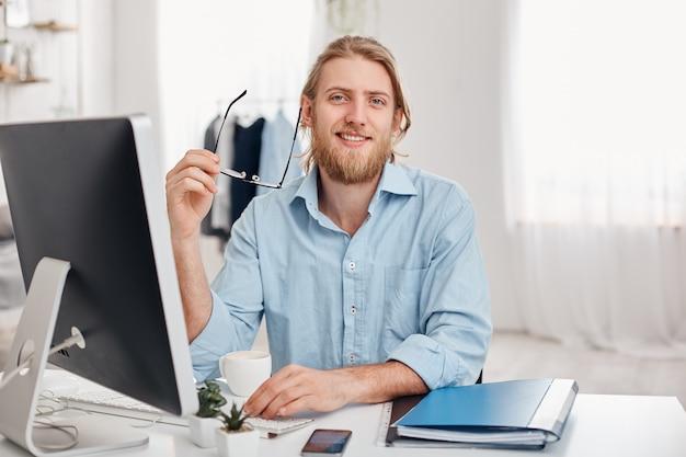 Bonito alegre barbudo jovem redator masculino de cabelos louro digita informações para publicidade no site, veste camisa azul e óculos, senta-se no escritório de coworking na frente da tela. Foto gratuita