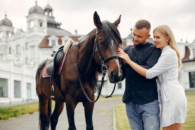 Bonito casal apaixonado com cavalo no rancho Foto gratuita