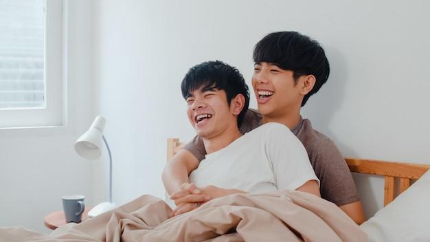 Bonito casal gay asiático falando na cama em casa. jovem asiático lgbtq + cara feliz relaxar descansar juntos passar um tempo romântico depois de acordar no quarto na casa moderna de manhã. Foto gratuita