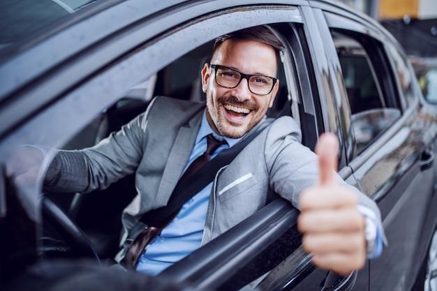 Bonito caucasiano com barba elegante empresário no terno e com óculos, segurando a mão no volante e dando os polegares. Foto Premium