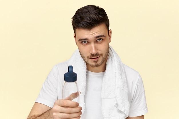Bonito e confiante jovem europeu com cerdas posando com uma toalha branca em volta do pescoço, bebendo água de um copo de plástico após o treinamento físico Foto gratuita