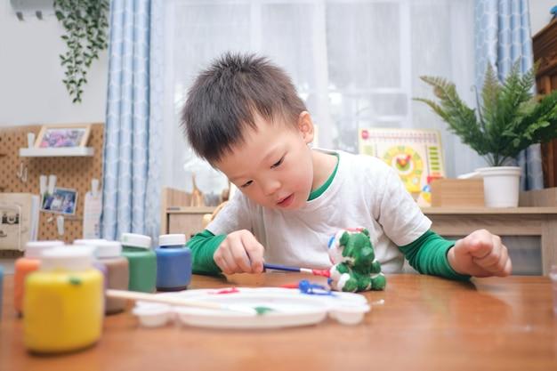 Bonito e feliz pequeno asiático de 3 a 4 anos de idade, criança, menino, criança pintando a cor em um brinquedo de gesso diy, estátua de gesso 3d interna em casa, conceito de jogo criativo para crianças e bebês - foco seletivo Foto Premium