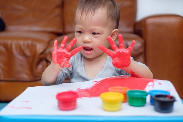 Bonito engraçado pouco asiático 18 meses / 1 ano de idade criança bebê menino criança pintura a dedo com as mãos e aquarelas, garoto pintura em casa, jogo criativo para crianças, conceito de educação montessori Foto Premium