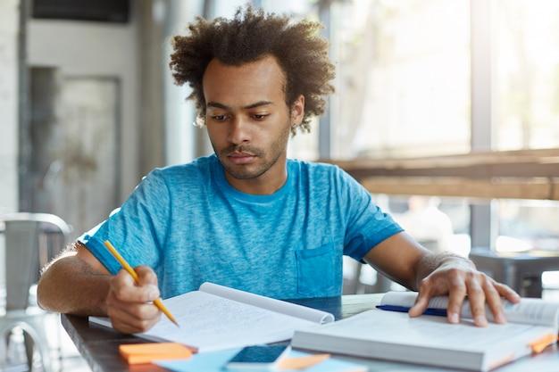 Bonito estudante afro-americano de pós-graduação com penteado encaracolado sentado à mesa com livro e caderno, estudando informações e notas, preparando-se para o exame ou prova, tendo um olhar focado e concentrado Foto gratuita