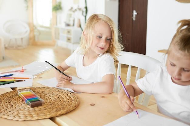 Bonito estudante fofo com cabelo loiro solto, segurando um lápis, tendo uma expressão facial curiosa, olhando para sua irmãzinha que está sentada ao lado dele, desenhando algo em uma folha de papel em branco Foto gratuita