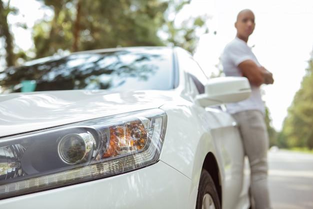 Bonito homem africano desfrutando de viajar de carro em uma viagem Foto Premium