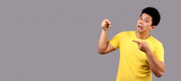 Bonito homem asiático com cara engraçada, segurando a tecla Foto Premium