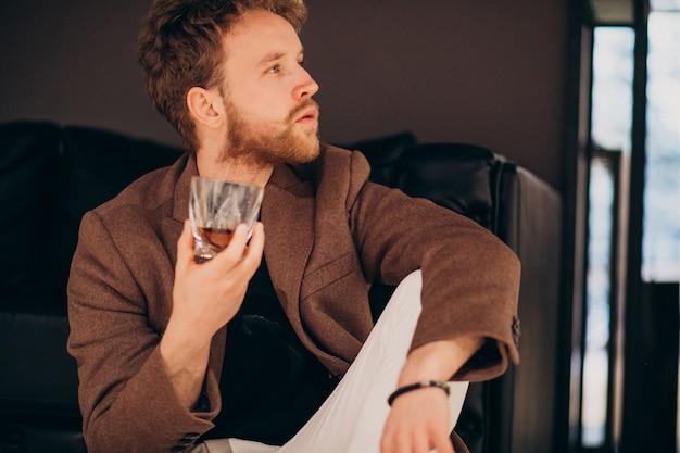 Bonito homem barbudo bebendo uísque Foto gratuita