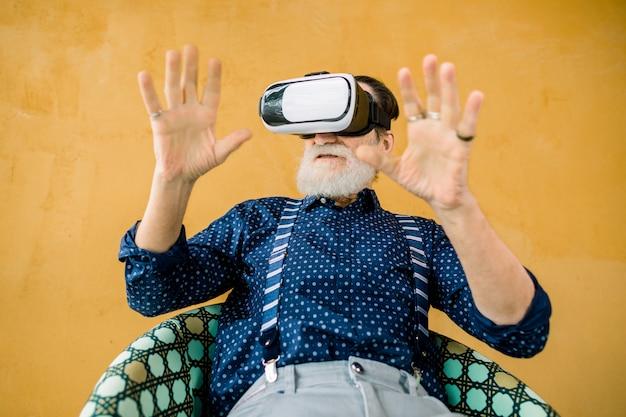Bonito homem barbudo sênior em roupas elegantes hipster, sentado na cadeira em fundo amarelo ee desfrutando de filme ou jogo em óculos de realidade aumentada Foto Premium