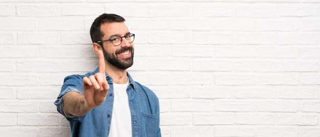 Bonito homem com barba ao longo da parede de tijolos brancos, mostrando e levantando um dedo Foto Premium