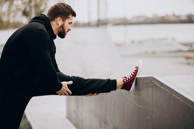 Bonito homem desportivo alongamento no parque junto ao rio Foto gratuita