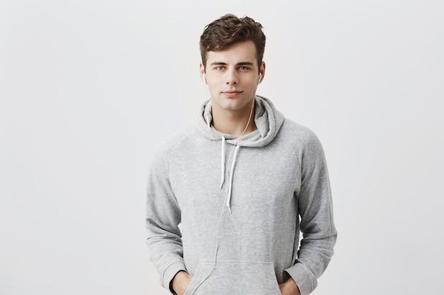 Bonito homem europeu atraente com capuz cinza, com as mãos nos bolsos, parece satisfeito, tem bom humor como chega em casa depois do trabalho. poses de estudante do sexo masculino bonito. Foto gratuita
