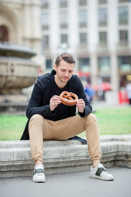 Bonito, homem jovem, segurando, pretzel, e, relaxante, parque Foto Premium