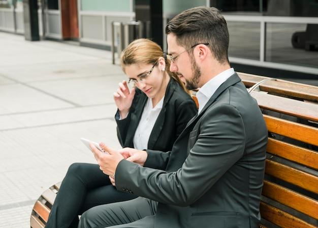 Bonito, homem negócios, mostrando, algo, ligado, telefone móvel, para, dela, colega Foto gratuita