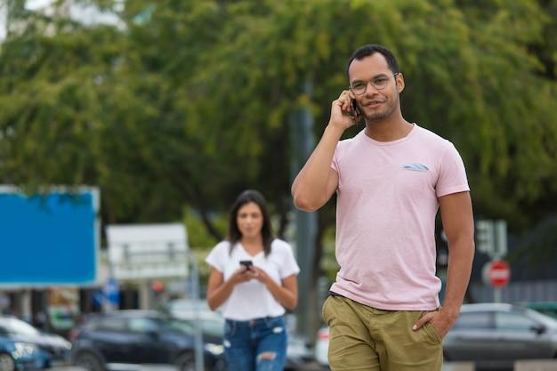 Bonito homem sorridente, falando no telefone enquanto caminhava na rua Foto gratuita