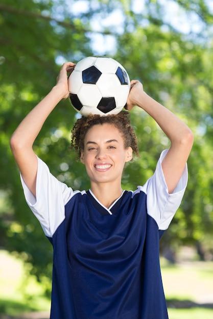 Bonito jogador de futebol sorridente da câmera Foto Premium