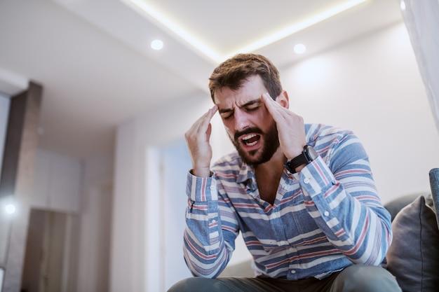 Bonito jovem barbudo sentado no sofá da sala, segurando a cabeça e tendo dor de cabeça. Foto Premium