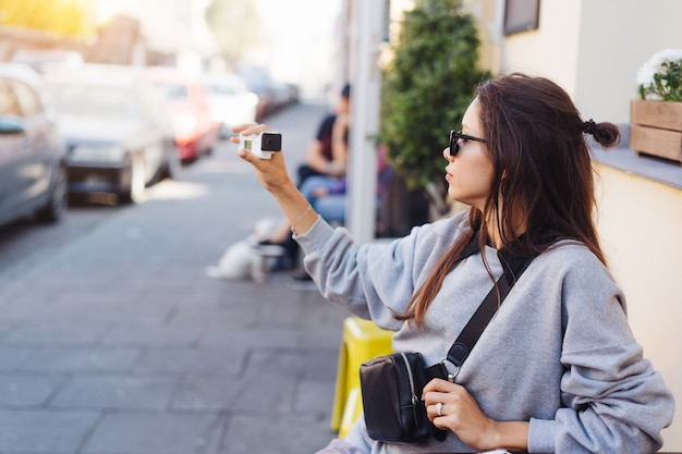 Bonito, jovem blogueiro feminino posando na câmera. Foto gratuita