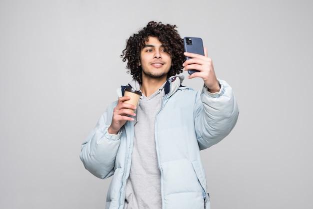 Bonito jovem confiante encaracolado tomando uma selfie, segurando a xícara de café para viagem em pé isolado sobre a parede cinza Foto gratuita