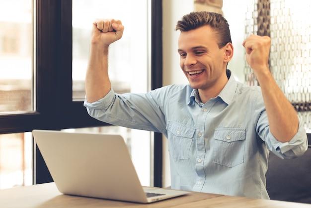 Bonito jovem empresário bem sucedido está levantando as mãos Foto Premium