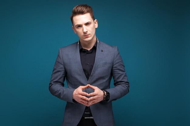 Bonito jovem empresário em jaqueta cinza, relógio caro e camisa preta Foto Premium