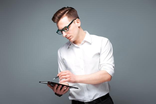 Bonito jovem empresário em relógio caro, óculos escuros e camisa branca segurar o tablet e caneta Foto Premium