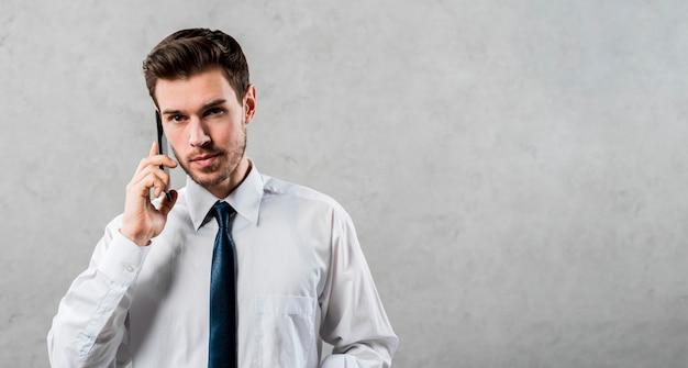 Bonito jovem empresário falando no celular contra parede cinza Foto gratuita