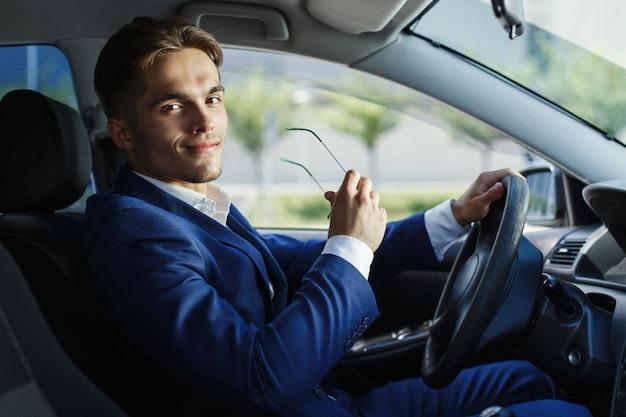 Bonito jovem empresário senta-se no volante dentro do carro Foto gratuita