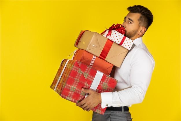 Bonito jovem europeu está segurando pesados presentes embalados e presentes Foto gratuita