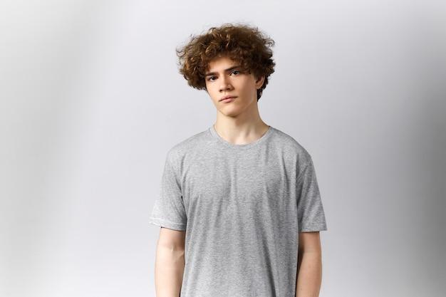 Bonito jovem europeu vestindo uma camiseta cinza em branco com espaço de cópia para o seu modelo, impressão ou desenho, olhando para a câmera com uma expressão séria Foto gratuita