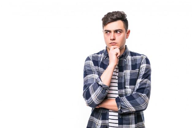 Bonito jovem pensativo isolado sobre parede branca Foto gratuita