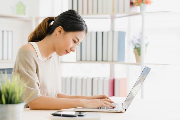 Bonito, jovem, sorrindo, mulher asian, trabalhando, laptop, escrivaninha, em, sala de estar, casa Foto gratuita
