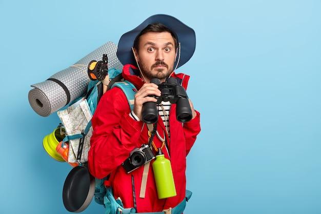 Bonito jovem turista do sexo masculino segura binóculos, caminha pela floresta, usa roupas casuais, carrega coisas necessárias para viajar, gosta de passar as férias com roupas esportivas Foto gratuita
